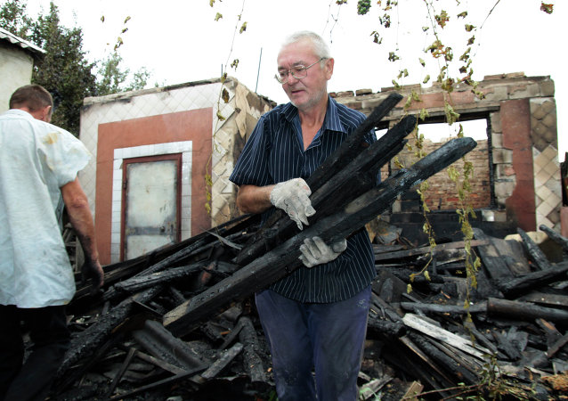 Hombre cerca de su casa destruida en la región de Donetsk
