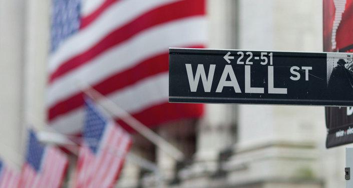 Una señal de Wall Street con unas banderas de EEUU de fondo