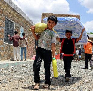 Niños yemeníes llevan la ayuda humanitaria (archivo)