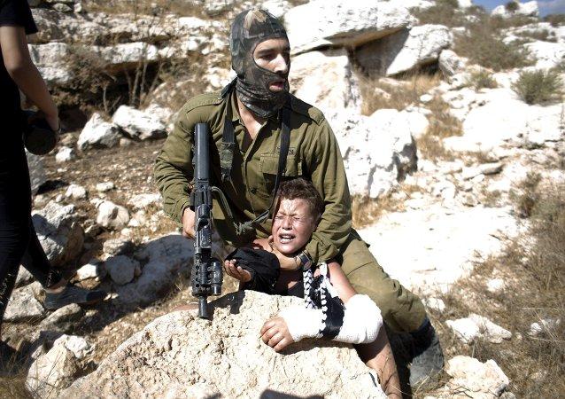 Un soldado israelí detiene a un niño palestino durante una protesta en la aldea cisjordana de Nabi Saleh