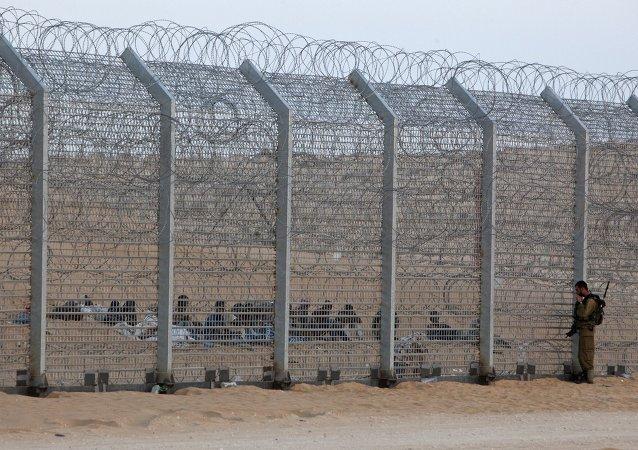 Inmigrantes africanos se sientan detrás de la valla fronteriza entre Israel y Egipto
