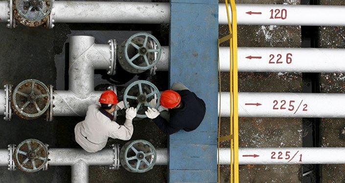 Trabajadores de una refineria de petróleo en Jingmen, China