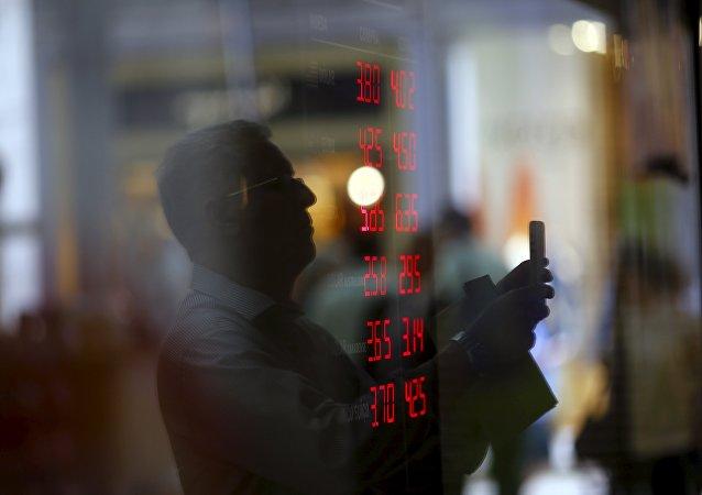 Reflejo de un hombre en el vidrio mientras toma imágenes de un tablero que muestra tipos de cambio de dólares y otras divisas