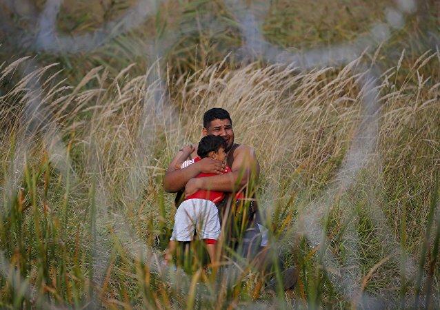 Migrante con su niño en Asotthalom, Hungría