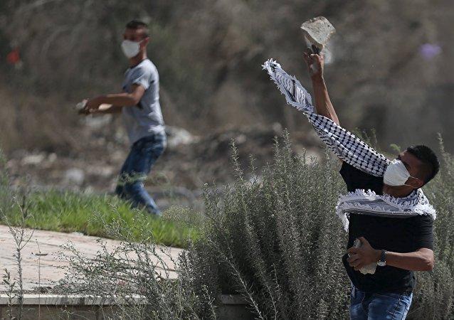 Jovenes palestinos están tirando piedras en las tropas de Israel