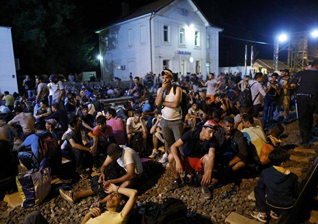 Migrantes están esperando cerca de la estación en Tovarnik, Croacia