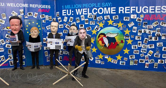 Actores disfrazados de David Cameron, Angela Merkel, Francois Hollande, Mariano Rajoy y Viktor Orbán cerca del retrato de Aylan Kurdi