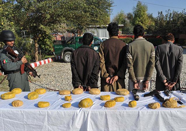 Policías afganos y los sospechosos arrestados por llevar heroína