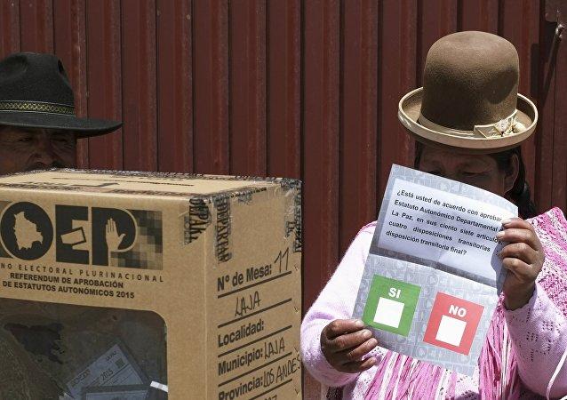 Miembro del comité de votación tiene una papeleta de votación durante un referéndum en Bolivia