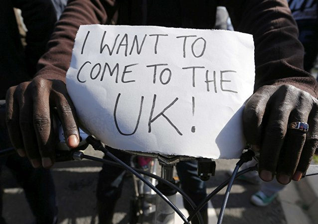 Migrante con un póster que dice Quiero llegar al Reino Unido!