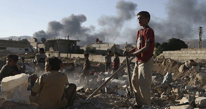 Niños sirios inspeccionan los escombros de una casa en la provincia de Damasco