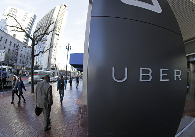 In this photo taken Tuesday, Dec. 16, 2014, people go past the headquarters of Uber in San Francisco.