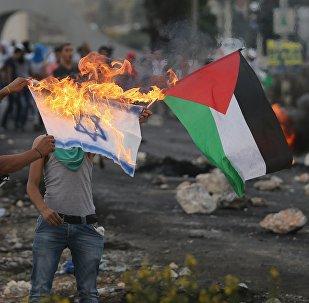 Manifestante palestino quema una bandera israelí