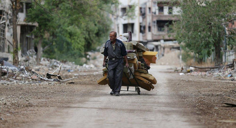 Hombre acarrea colchones en Jobar, Siria
