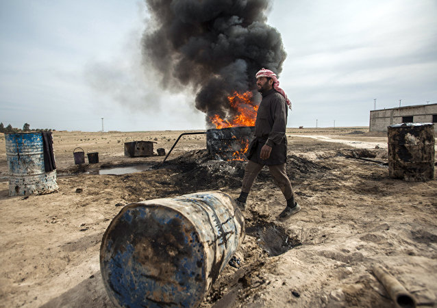 Un hombre trabaja en una refinería de petróleo improvisada en Raqqa