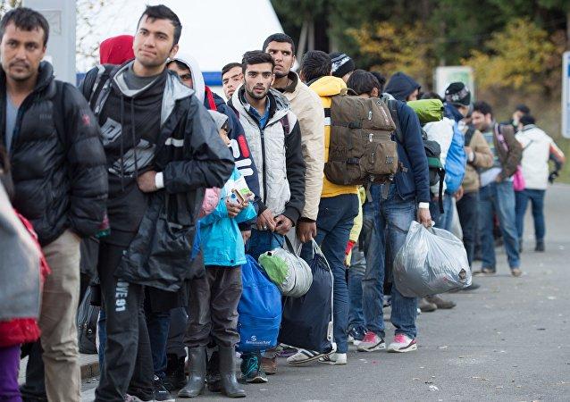 Refugiados esperan en la cola tras cruzar la frontera entre Alemania y Austria