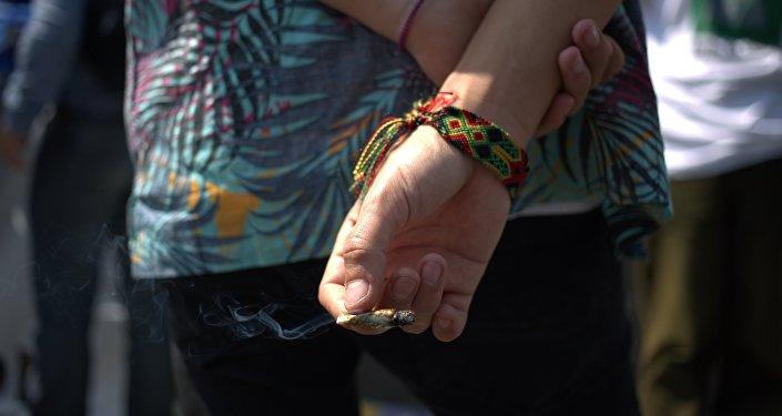 Partidario de la legalización de la marihuana tiene un cigarrillo fuera de la Corte Suprema, México