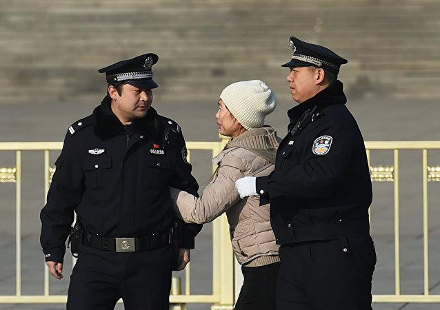 Policías chinos detienen a una mujer en Pekín