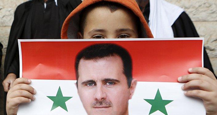 Un niño con la bandera de Siria con la foto de Bashar Asad en sus manos