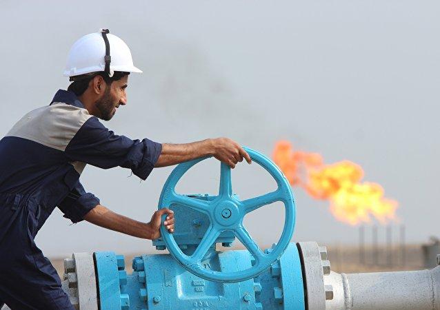Empleado comprueba una tubería de petróleo en Irak