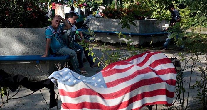 Migrantes cubanos cerca una toalla con la bandera de EEUU en Peñas Blancas, Costa Rica