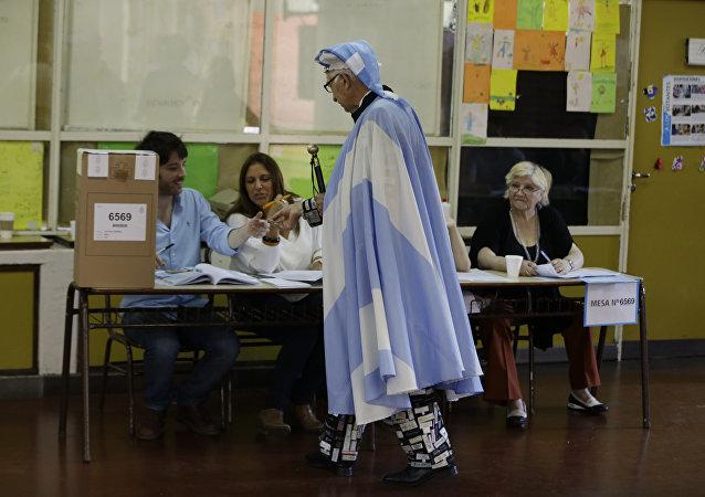 Un votante envuelto en una bandera argentina presenta su identificación en un puesto de votación durante la segunda vuelta de las elecciones presidenciales en Buenos Aires, Argentina, noviembre de 2015