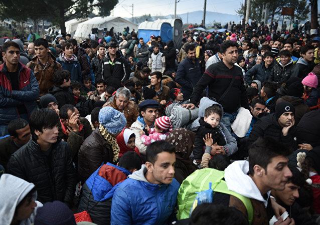 Refugiados esperan para poder cruzar la frontera entre Macedonia y Grecia