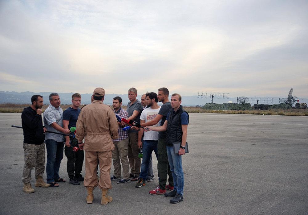 Спасенный летчик Су-24 Военно-космических сил России капитан Константин Мурахтин (в центре) отвечает на вопросы журналистов на авиабазе Хмеймим в сирийской Латакии