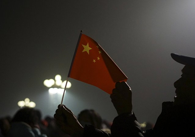 Los ciudadanos con la bandera de China en la Plaza de Tiananmén cubierta de bruma industrial