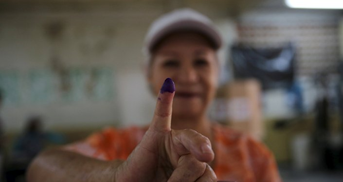 A women shows her ink-stained finger after casting her vote during a legislative election, in Caracas December 6, 2015