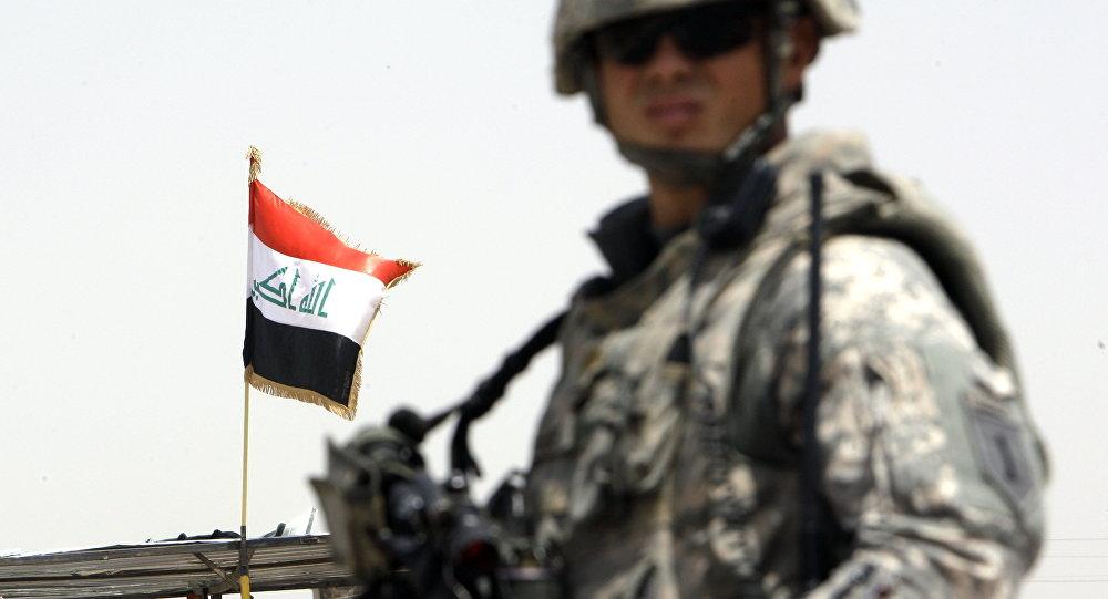 Soldado estadounidense enfrente de la bandera de Irak