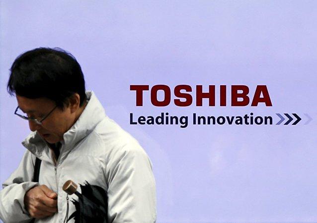 Un hombre pasa por un logo de la empresa japonesa Toshiba