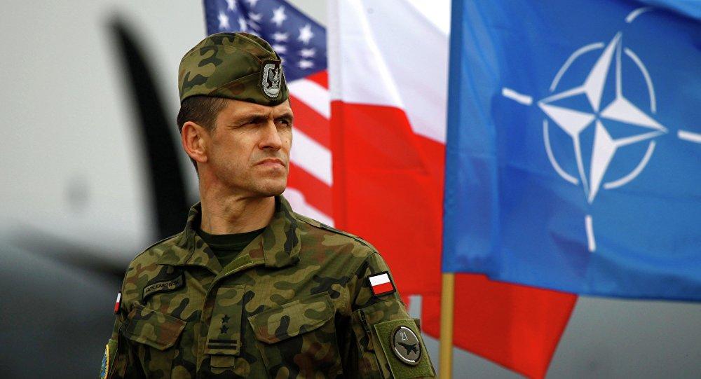Soldado polaco cerca de banderas de Polonia y OTAN