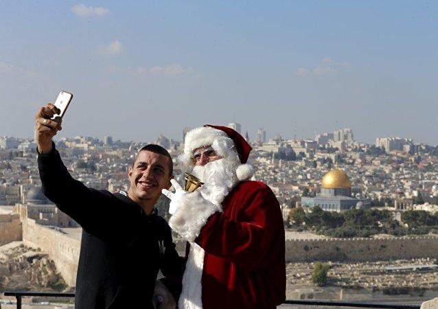 Un hombre se hace un selfie con Papá Noel en Jerusalén