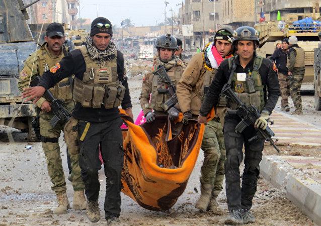 Miembros de las fuerzas de seguridad iraquíes llevan el cuerpo de un militar en Ramadi