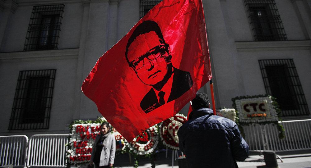Un hombre alza la bandera con la cara de Salvador Allende frente al Palacio de La Moneda en Chile