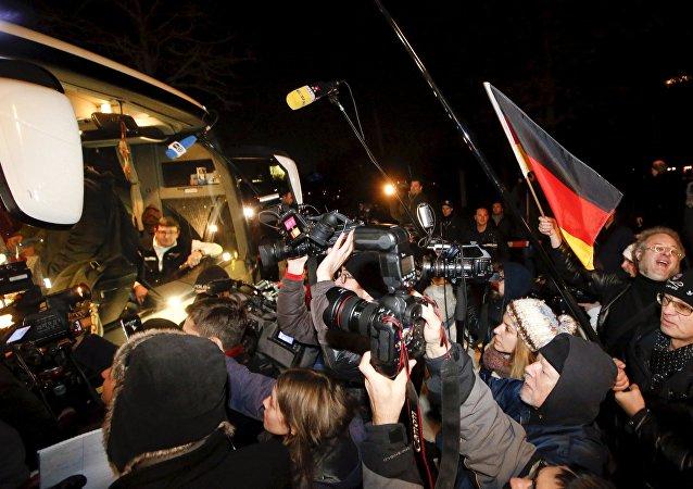 Prensa y manifestantes cerca del autobús con los refugiados de Bavaria tras su llegada a Berlín
