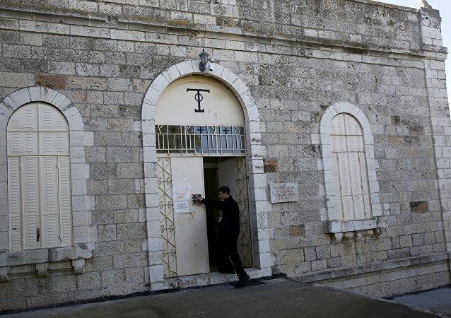 Un monje trata de limpiar las pintadas de la puerta de la Abadía de la Dormición de Jerusalén