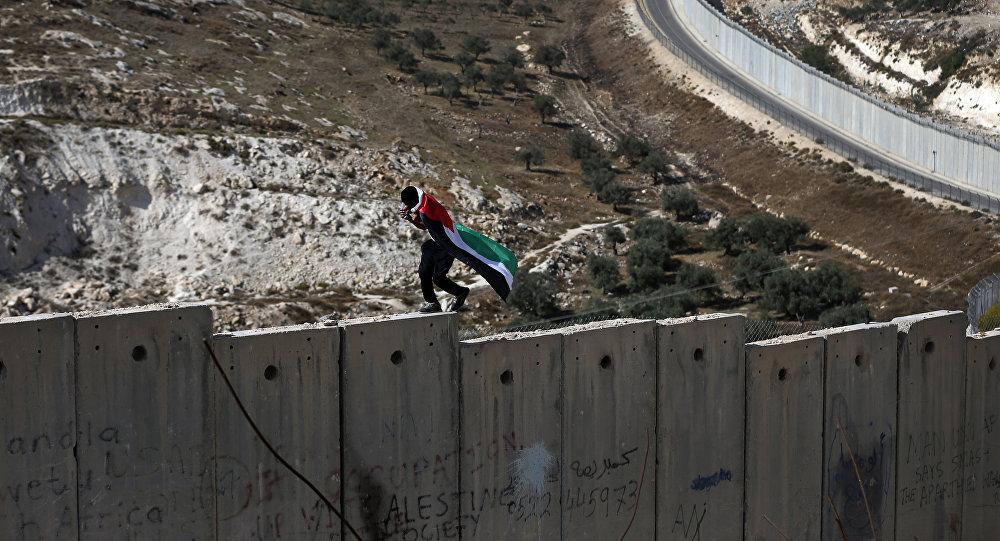 Un palestino camina sobre el muro de Cisjordania