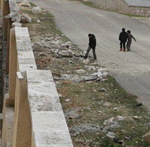 Niños sirios cerca de una escuela destruida en Alepo