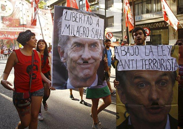 Los manifestantes con los posters con el president Macri durante una protesta