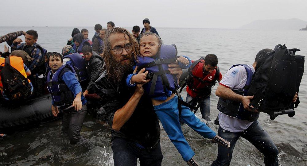 Un voluntario lleva a una pequeña refugiada siria tras un naufragio cerca de las costas de Turquía