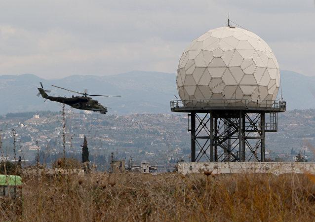 Un helicóptero vuela cerca de un radar en la base militar rusa Hmeymim en Siria