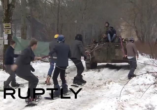 Mientras tú trabajas, rusos practican snowboard tras un vehículo militar