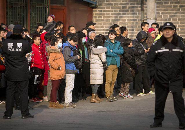 Policías chinos viendo los depositantes de Ezubao reunirse fuera de la Oficina Estatal de Cartas y Llamadas en Beijing