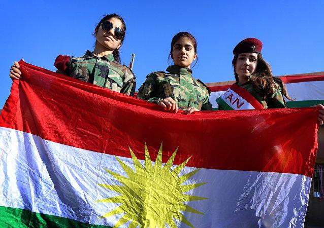 Jóvenes kurdas llevan la bandera de Kurdistán en Irak