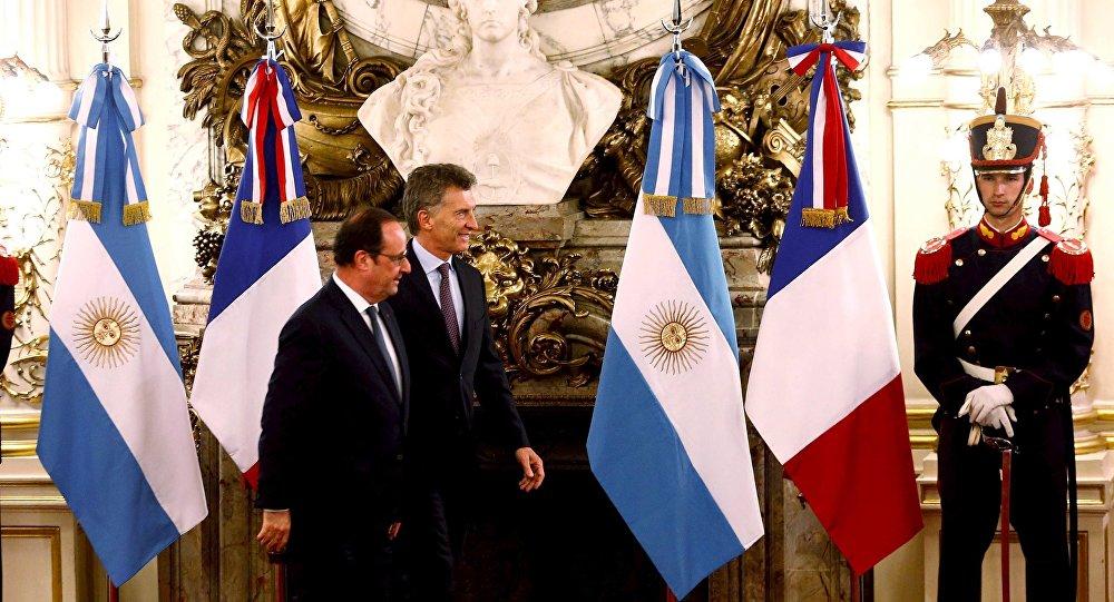 El presidente de Francia, François Hollande, con el presidente de Argentina, Mauricio Macri frente a las banderas nacionales de ambos paises