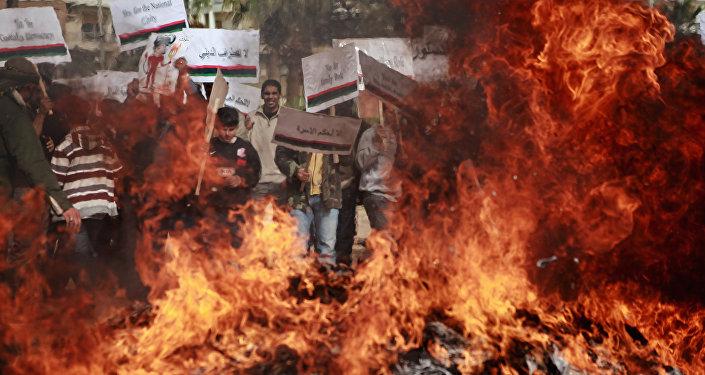 Protestantes queman los retratos de Muamar Gadafi