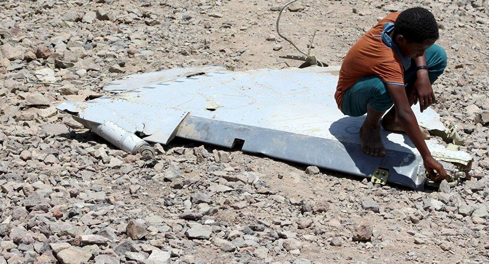Un niño sentado en un fragmento del avión de Emiratos Arabes estallado en Yemen