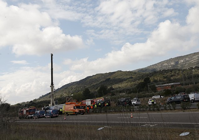 Emergency and rescue teams work at the scene of a traffic accident in Freginals, Spain